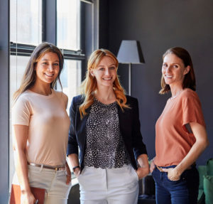 Portrait of happy businesswomen standing by window. Smiling female professionals are in brightly lit creative office. They are wearing smart casuals.