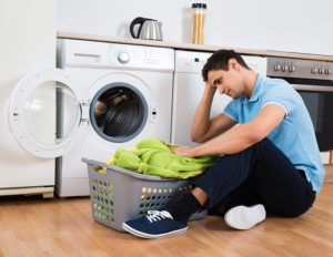 Tensed young man looking at laundry basket at home